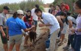 International students look at a marine creature caught during a net fishing program