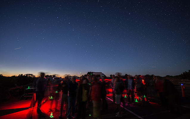 people and a telescope illuminated in red with stars overhead