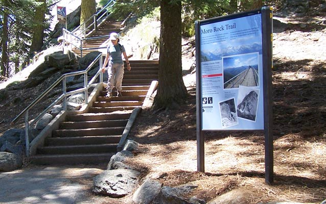 An upright orientation exhibit near a granite staircase