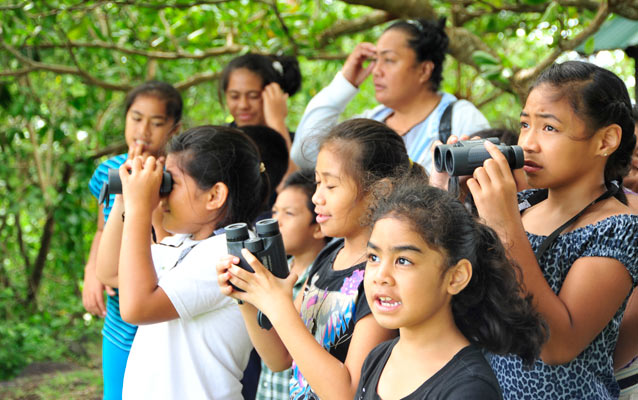 Photo of elementary students using binoculars to watch native birds.