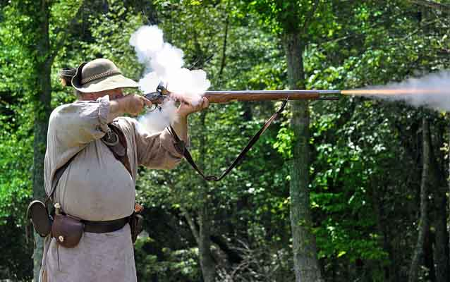 Smoke rises from the lock and fire shoots from the end of a musket as a reenactor fires.