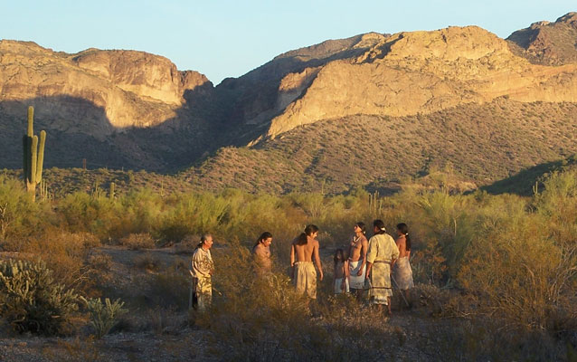 Actors in costumes from the Hohokam era stand in a circle in front of the Superstition Mountains