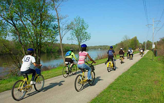 High school students bicycle along a beautiful paved trail along the Schuylkill River.