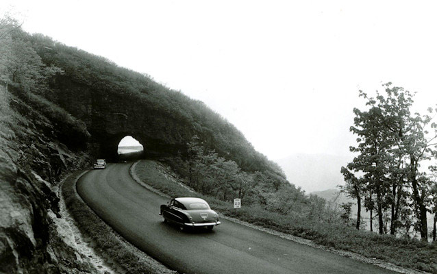 Historic photo from the mid 20th century of cars driving along the Blue Ridge Parkway.