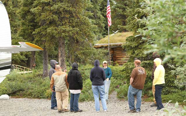 K. Schubeck, a volunteer at the remote Proenneke Historic Site for 13 years, gives a tour for wounded veterans and their spouses.
