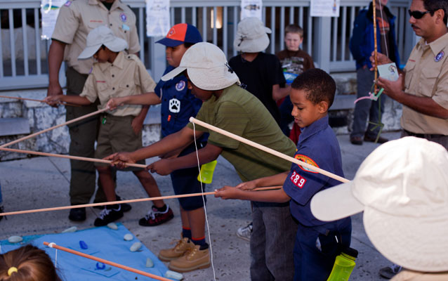 Children wearing Lancelot Jones-style fishing hats use simple poles to learn about being a fishing guide.