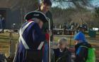 A reenactor brings the Revolutionary War to life for 2 young children and their dad.