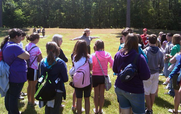 Park ranger gestures toward earthworks while talking to students