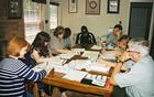 Park employees sit around a table in the administrative office and work on an assignment.