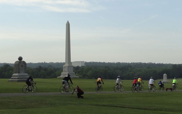 Bicycles ride past a series of stone monuments