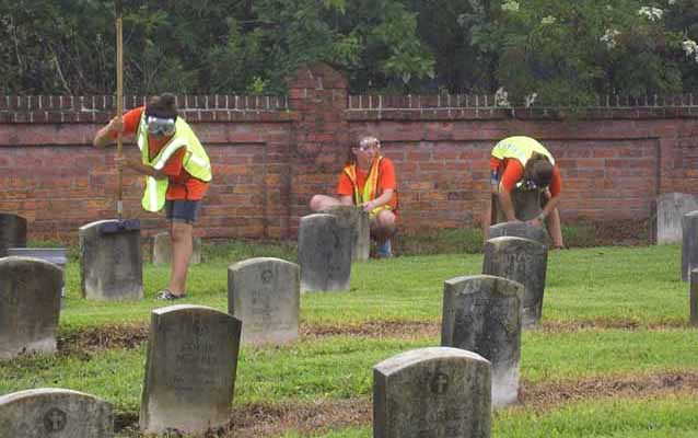 Image of volunteers scrubbing headstones at a national cemetery