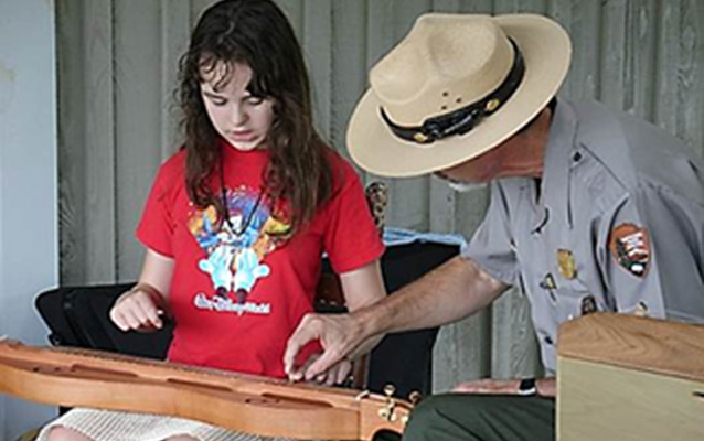 A ranger helps a young girl play a lap dulcimer in a Parks As Classrooms program.