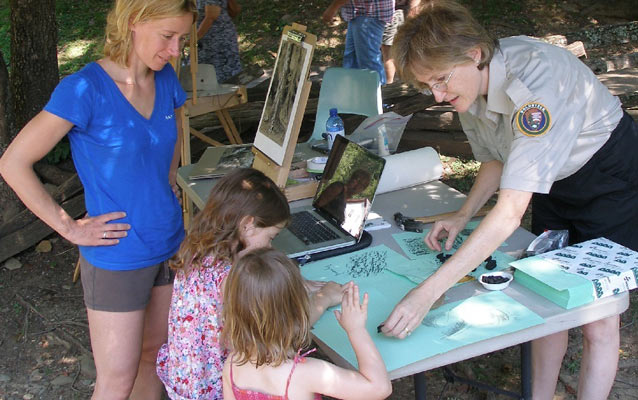 Artist in Residence, Kelly Adams, helps young park visitors with charcoal drawing techniques.