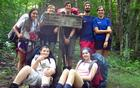A group of young backpackers poses by a trailhead sign in the park.