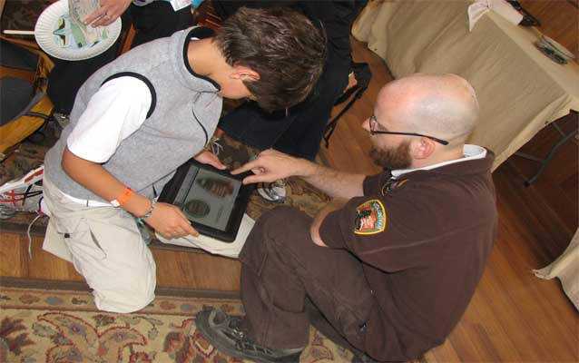 Volunteer and child look at iBook on tablet computer