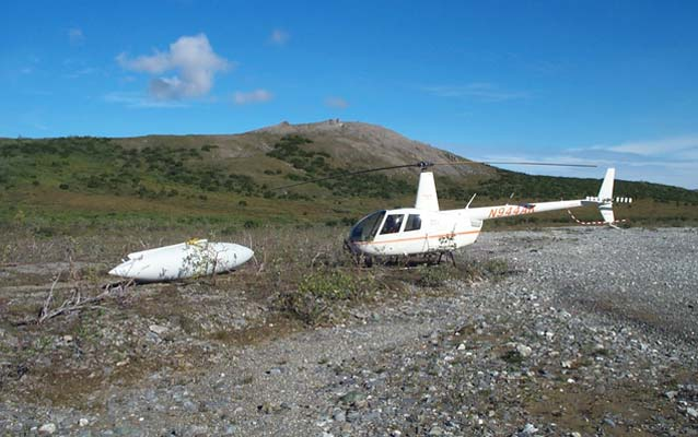helicopter sits next to discarded, 1970s-era fuel pod
