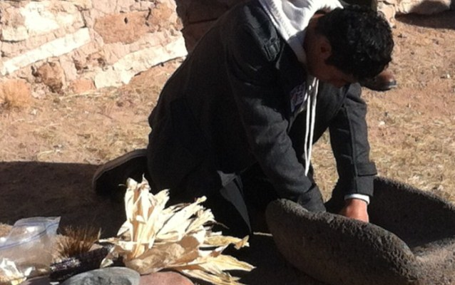 OMK youth grinds corn before making a digital story