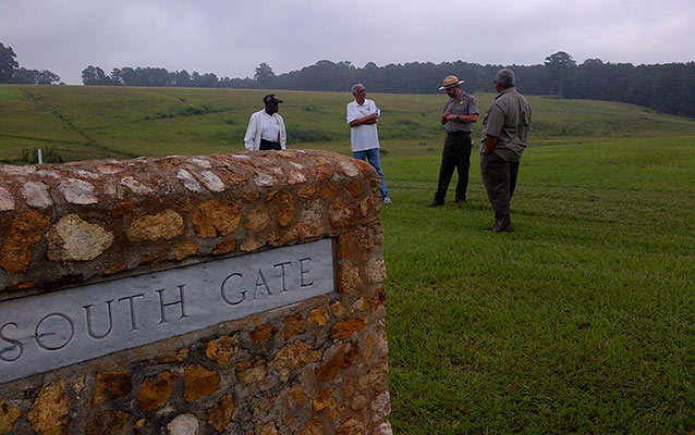 Park ranger and men stand in an open field area behind a stone monument labeled