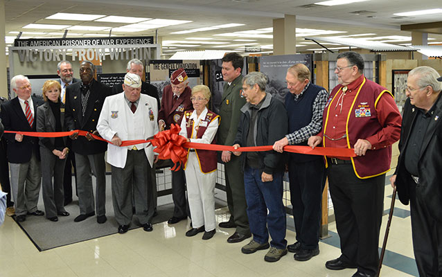 A group of people stand by exhibit panels and cut a red ribbon.