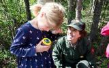 Park ranger smiles as she watches a child looking into a magnifying box