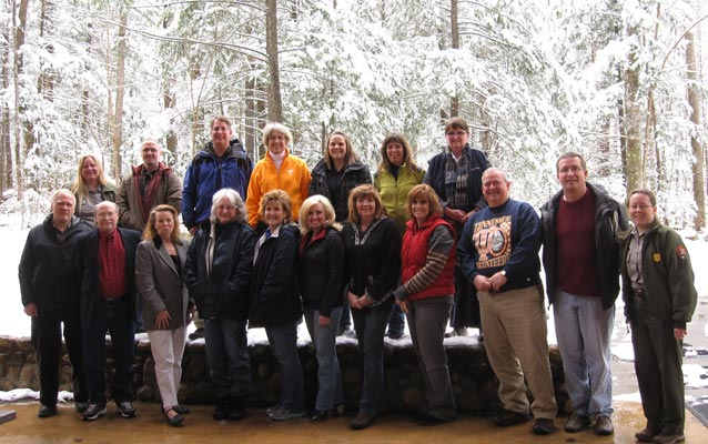 Group picture of teacher workshop participants standing in front of snowy woods.