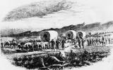 A black and white illustration shows numerous wagons and oxen with men walking and some riding horses.