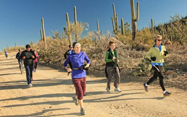 BEYOND participants running on a dirt road among the saguaro cactus in Saguaro National Park