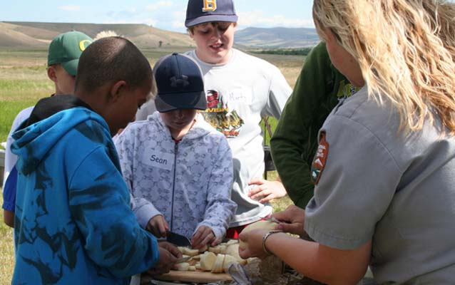 Kids preparing food for campfire cooking program.