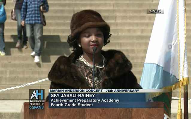 dc school student stands in front of podium in fur hat and shawl