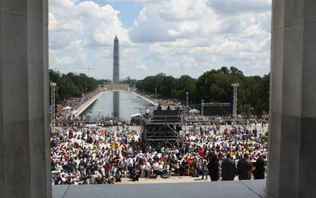 crowd stands on the lincoln memorial plaza with washington monument in the background