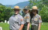 Three park rangers with the watergap behind them