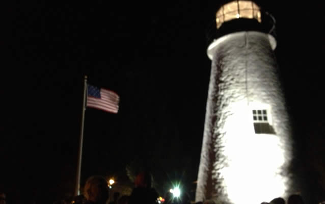 Nightime view of lighthouse with American flag