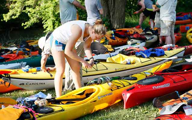 A young woman prepares her kayak for a day on the water.