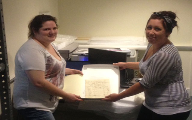 Park Interns Caroline Davis and Kaylah Rodriguez with the 1860 Stone Family Census Record