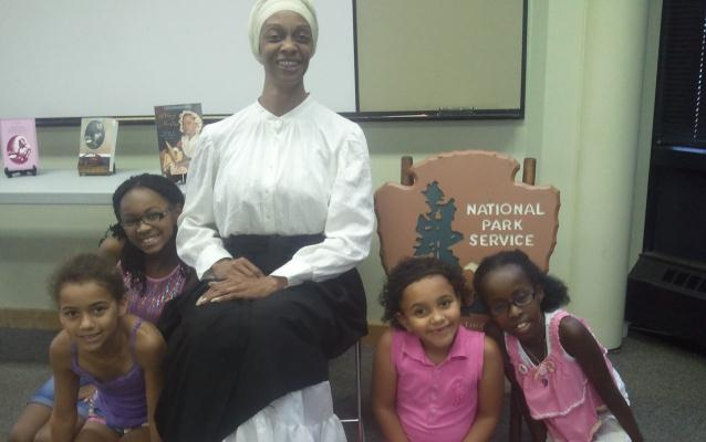 Denise Valentine, portraying Phillis Wheatley, sits with young girls after her writing program