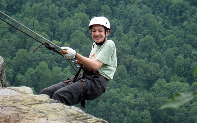 Teenage boy rappels down a cliff face