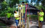 Four youth build and hang a bamboo windchime.
