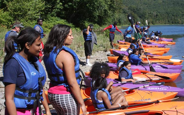 Students standing by kayaks on the Delaware River