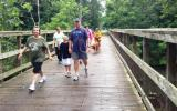 A family walks across a wooden bridge in a forest
