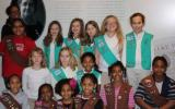 Girl Scouts pose in front of a large photo of Maggie Walker