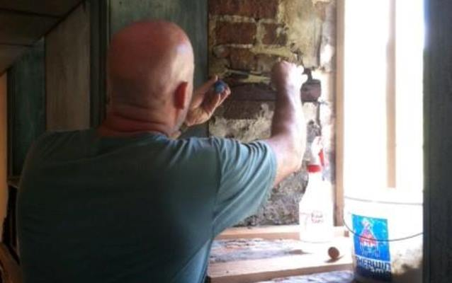 Park service employee working on bricks framing a historic window