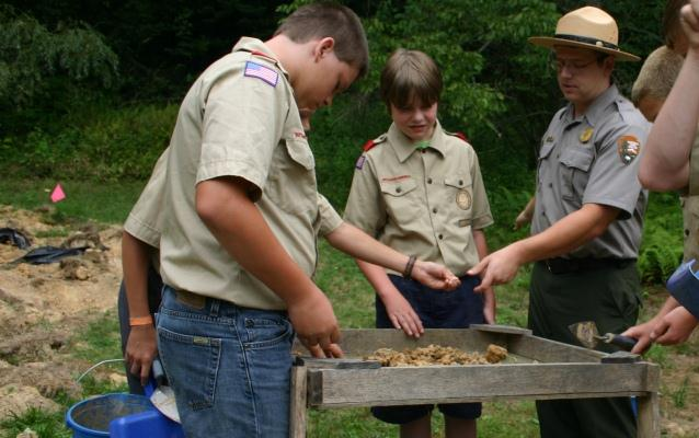 Boy Scouts and a Park Ranger looking for artifacts