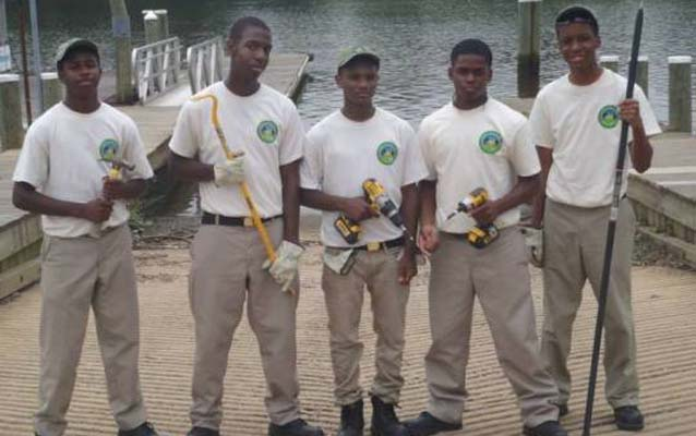 Five Chesapeake Youth Corps participants pose in front of the new universally accessible boat launch they helped build.
