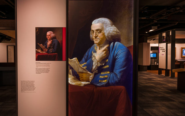 Benjamin Franklin Museum exhibit panel featuring Franklin's image in the foreground; museum in the background.