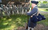 Colonial Minute Man re-enactor talking to National Guard unit.