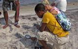 Students use a magnifying glass to take a closer look at sand grains.