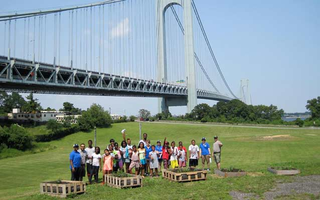 A group of students stand near the Verrazano bridge