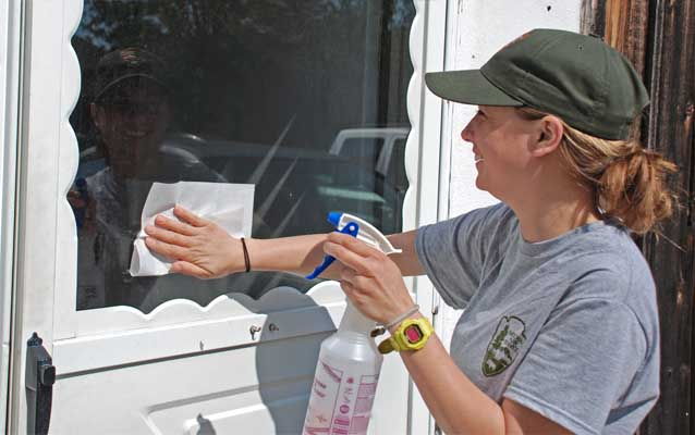 A Fire Island National Seashore staff member uses green cleaning solution to clean a window.
