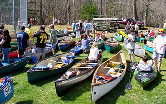 Assembling at a baseball field, a group of canoers get ready to embark.