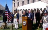 Surrounded by soldiers and American flags, Senator Gillibrand and Brand USA's Mike Fullerton present at a podium in front of an old stone fort.